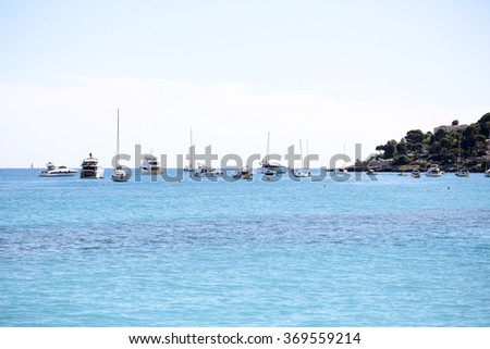 Photo of yachts sailing boats sea vessels in harbor seacoast in calm blue sea silhouetted against clear light sky day time on seascape background, horizontal picture - stock photo