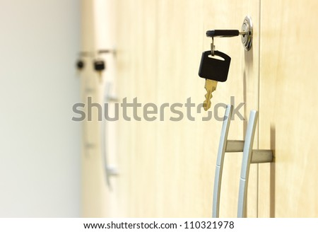 Photo of yellow wooden closets with black keys plugged in.Small depth of field - stock photo