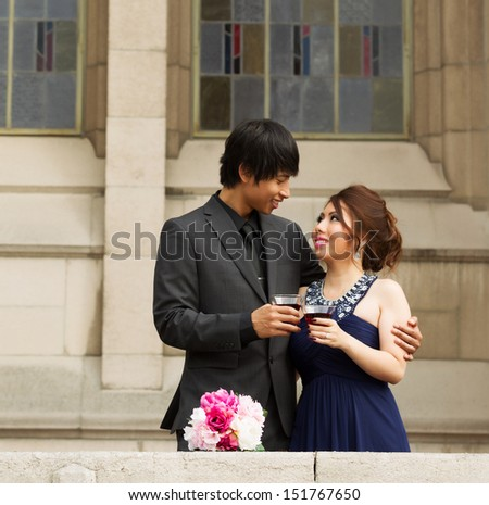 Photo of young adult couple, man holding his lady, sharing a social drink together with building in background