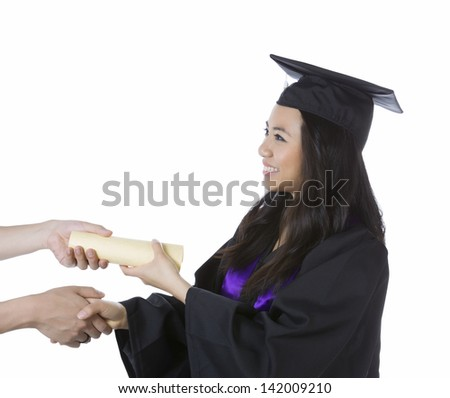 Photo of young adult woman, dress in graduation gown and cap, receiving her diploma in one hand while shaking with her other hand on a white background