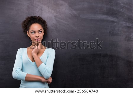 Photo of young afro-american woman on blank chalkboard background. Woman smiling and looking aside - stock photo