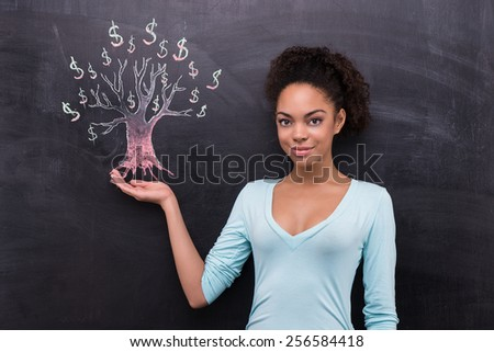 Photo of young afro-american woman on chalkboard background. Woman looking at camera. Dollar tree painted on chalkboard - stock photo