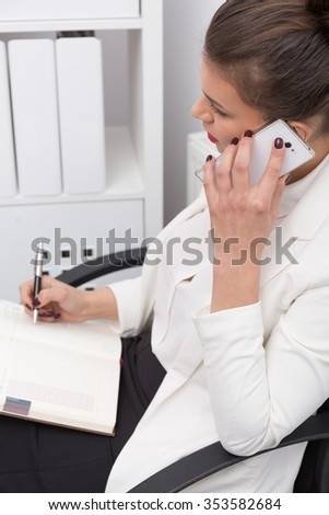 Photo of young and attractive female manager talking on phone