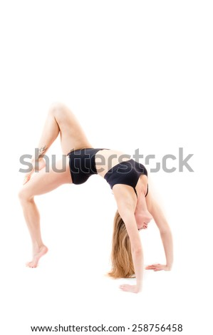 Photo of young athletic flexible girl in black suit on white background doing bridge