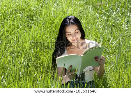 Photo of young attractive brunette woman sitting on grass and reading old magazine