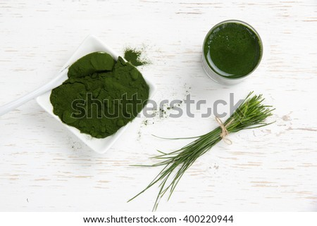 Photo of young barley powder and drink with grass bunch on white wooden surface; concept of superfood - stock photo