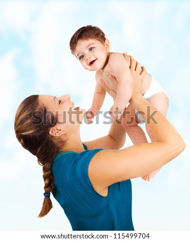 Photo of young beautiful mother with cute baby boy, smiling mommy lift her adorable son, pretty woman throwing up cheerful little child on blue sky background, happy healthy family, love concept - stock photo