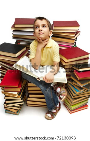 Photo of young boy reading a book while sitting on books - stock photo
