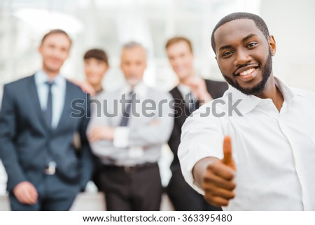 Photo of young businessman and his colleagues. Businessmen and business woman working in office with big window. Men and woman smiling and looking at camera. African businessman showing thumb up - stock photo