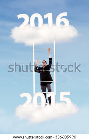 Photo of young businessman climbing stairs on the cloud toward numbers 2016 - stock photo