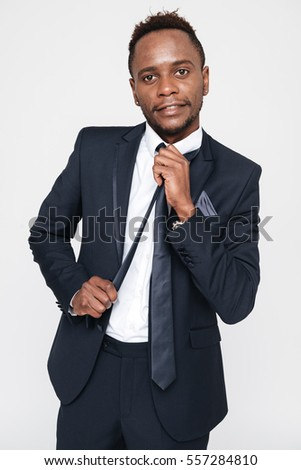 Photo of young businessman standing in studio. Isolated over white background. Look at camera.
