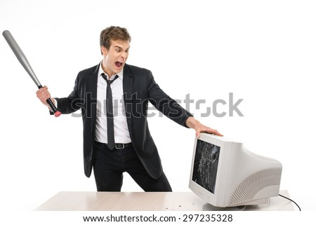 Photo of young businessman wearing suit, screaming and breaking with baseball bat computer monitor. Isolated on white background