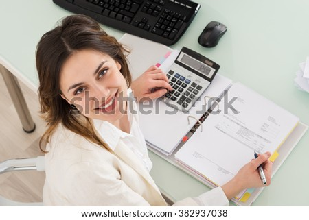 Photo Of Young Businesswoman Calculating Invoice In Office - stock photo