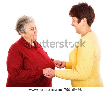 Photo of young caregiver holding elderly woman hands