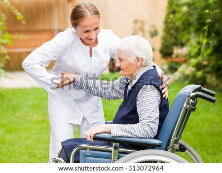 Photo of young carer helping the elderly woman - stock photo