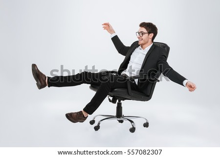 Photo of young caucasian businessman sitting on chair at studio. Isolated over white background. Look aside.