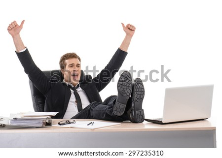 Photo of young cheerful businessman wearing suit. He sitting with his feet on desk with arms up. Isolated on white background - stock photo