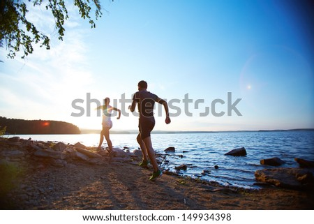 Photo of young couple running on the coastline - stock photo