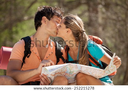 Photo of young couple sitting on a big rock in the mountains and kisses each other - stock photo