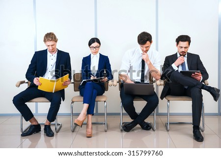 Photo of young creative business team of four with documents and computers. They sitting in a row and working