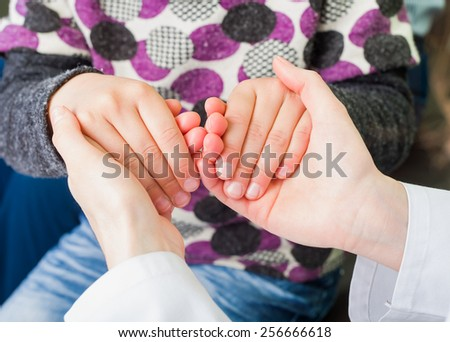 Photo of young doctor hands holding the child hand - stock photo