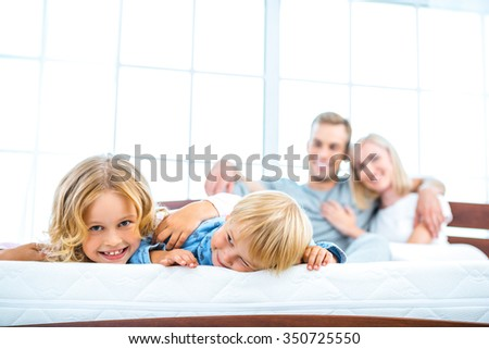 Photo of young family of four lying on nice white bed. Young family demonstrating quality of mattress - stock photo