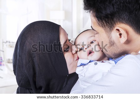 Photo of young father and mother hugging their baby and kissing his cheeks at home - stock photo