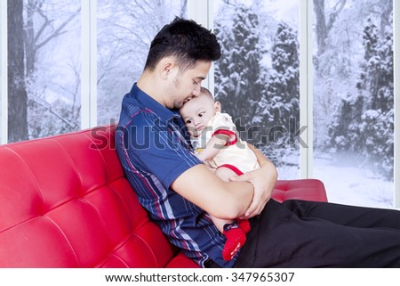 Photo of young father sitting on the sofa while holding his baby for making a good relation