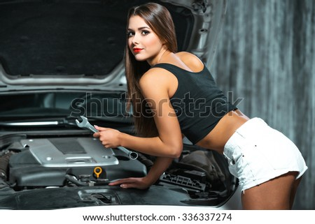 Photo of young female car repair worker. Glamour sexy brunette wearing jean shorts. Girl with wrench looking at camera and working under car cowl - stock photo