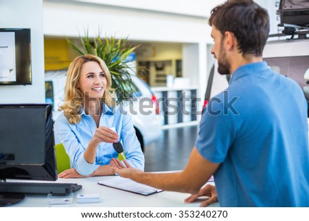 Photo of young female consultant and buyer. Young man buying new car in car showroom. Buyer receiving keys