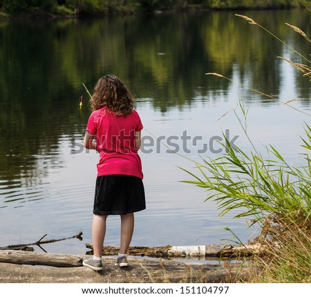 Photo of young girl, back to camera, scanning lake before casting with lake and trees in background and tall weeds to the right of her