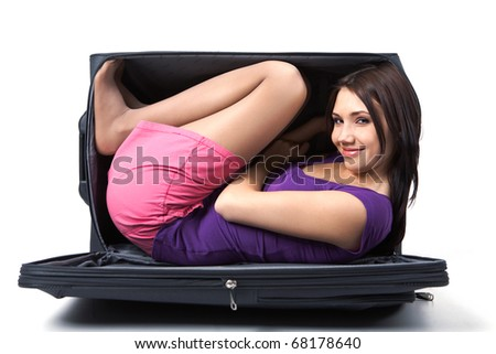 Photo of young girl with smile lying in a black suitcase - stock photo
