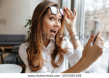 Photo of young happy business woman sitting indoors using mobile phone near window looking camera.