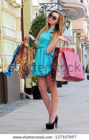 Photo of young joyful woman with shopping bags