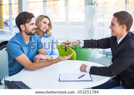 Photo of young male consultant and couple. Young woman and man buying new car in auto show. Buyer receiving keys. Concept for car rental - stock photo