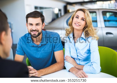 Photo of young male consultant and couple. Young woman and man buying new car in auto show. Concept for car rental - stock photo