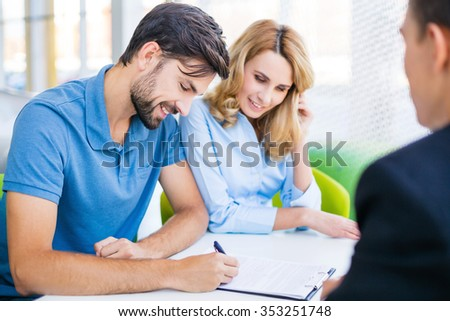 Photo of young male consultant and couple. Young woman and man buying new car in auto show. Signing of contract. Concept for car rental - stock photo