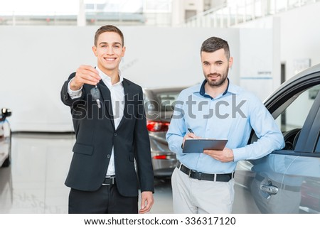 Photo of young male consultant presenting new car to buyer and holding keys in auto show. Concept for car rental