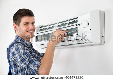 Photo Of Young Male Technician Repairing Air Conditioner