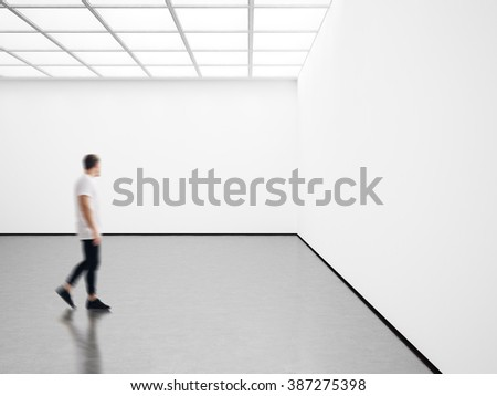 Photo of young man in modern gallery looking at the empty canvas. Blank mockup, motion blur  - stock photo