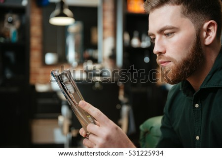 Photo of young man sitting in armchair at barbershop and reading magazine.