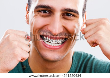 Photo of young man with braces using dental floss,Dental hygiene - stock photo