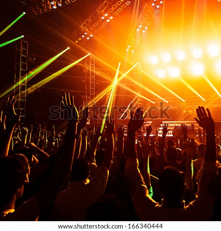 Photo of young people having fun at rock concert, active lifestyle, fans applauding to famous music band, nightlife, DJ on the stage in the club, crowd dancing on dance floor, night performance - stock photo