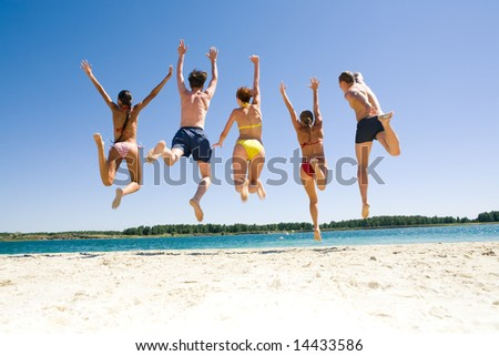 Photo of young peopleâ??s backs jumping on the sea shore simultaneously