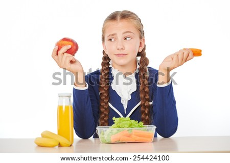 Photo of young school girl at lunch. Girl looking disappointed by her healthy lunch. Isolated on white background - stock photo