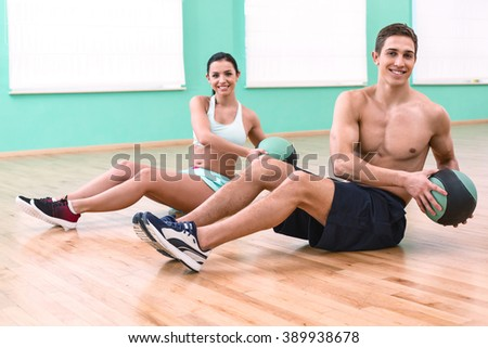 Photo of young sporty man and woman. Fitness people training with ball in sport club. Woman and man  smiling and looking at camera - stock photo