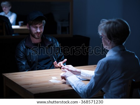 Photo of young suspect wearing cap responding to policewoman guestions - stock photo