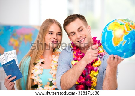 Photo of young tourists with hawaiian necklaces. Young man and woman smiling, holding tickets and passport. Couple choosing country on globe. Travel agency office interior with big world map - stock photo