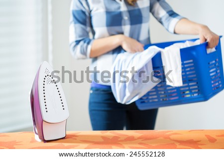 Photo of young woman bringing the clean laundry to iron - stock photo