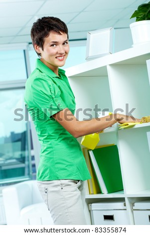 Photo of young woman dusting and looking at camera - stock photo